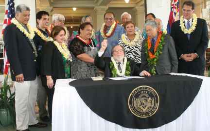 Hawaii's Governor uses an embroidered tablecloth when signing important legislation